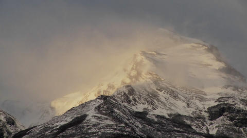 Snow blows off mountain peaks Stock Video Footage
