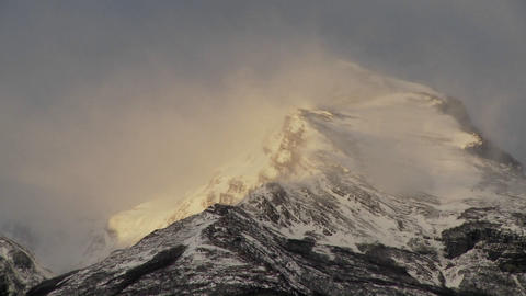 Snow blows off mountain peaks Footage