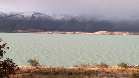 A glacial river flows beneath foggy mountains Footage