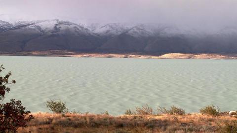 A glacial river flows beneath foggy mountains Stock Video Footage