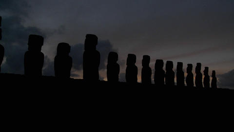 A long line of statues is silhouetted on Easter Island in this time lapse shot Footage