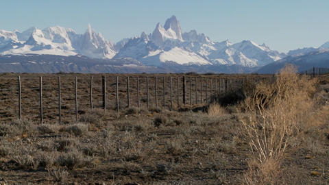 Pan across a fenced region in the far Southern region of Patagonia with the Fitzroy Range in backgro Footage