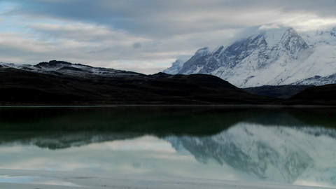 Pan across a beautiful lake in front of the peaks of... Stock Video Footage