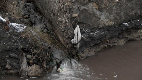 Polluted water flows into an irrigation ditch Stock Video Footage