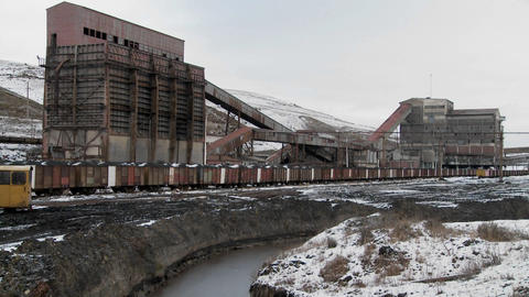 An abandoned mine with ore rail cars in the foreground Stock Video Footage