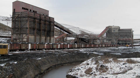 An abandoned mine with ore rail cars in the foreground Footage