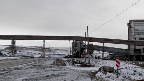 Pan across an old abandoned mine in winter with traffic passing on a road Footage