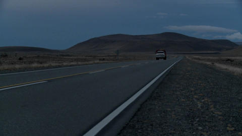 Side view of an old truck passing on a lonely road at dusk or night Footage