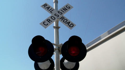 Red lights flash at a railroad crossing Footage