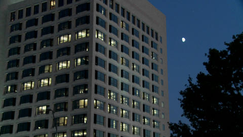 An office building at night with lights on inside Footage