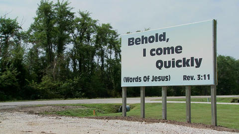 A large white sign quotes Jesus along a rural roadway Stock Video Footage