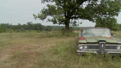 Pan to an old abandoned Ford Edsel sitting in a field Footage