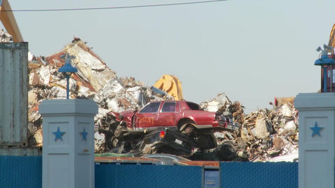 Cranes lift and move scrap metal around abandoned and destroyed cars in a junkyard or scrap metal ya Footage