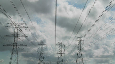 Time lapse of clouds moving behind high tension wires and power lines Footage