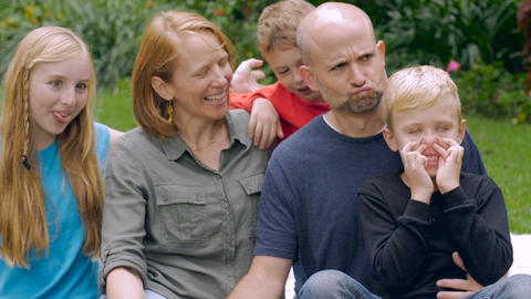 A family of 5 make funny faces together for a portrait outside in slow motion in Footage