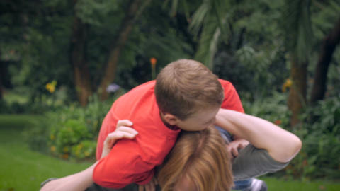 A red headed mother plays with her adorable young blond haired son on her should Footage
