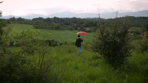 A man with a red umbrella walks off into the distance in a rural setting with mo Footage