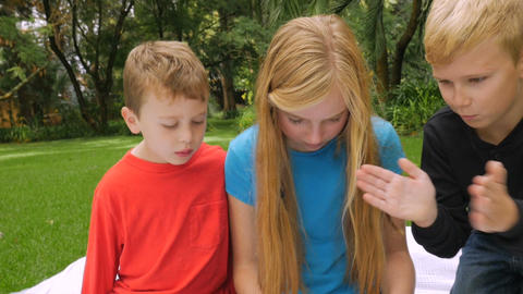 Three young, cute children play on a tablet outside while one swats a mosquito a Footage