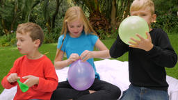Three young beautiful innocent kids blow up and tie off balloons outside - slowm Footage