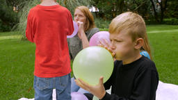 A redheaded mother and her 2 sons and daughter blow up balloons together outside Footage