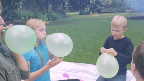 A mom blows up a balloon for her young, cute son at a picnic outside - slowmo st Footage