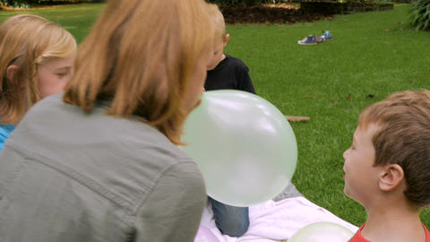 An adorable little boy looks at the camera as his mom blows up his balloon - slo Footage