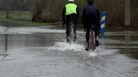 Cyclists riding on a flooded road, Water over road, Road flooded by the overflow Live Action