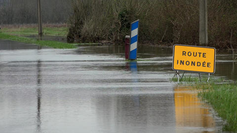 Water over road, Road flooded by overflow of a river and danger road sign Live Action