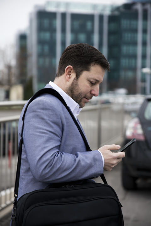 Businessman using smartphone Outdoors in front of Office Building. Texting, Sms, Internet Surfing, Fotografía