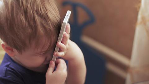 Child boy speaks on smartphone Live Action