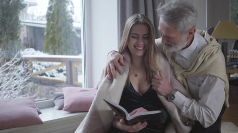Middle-aged Caucasian man covering reading young woman with blanket. Cheerful Live Action