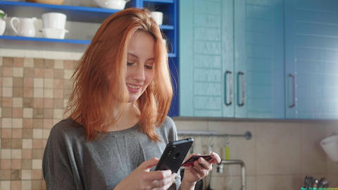 Attractive girl with red hair makes a purchase in the online store using a Live Action