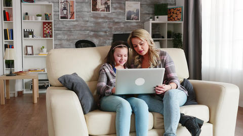 Young mother using laptop for her daughter education Live Action