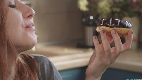 Attractive hungry red-haired girl eats a donut in the early morning on the Live Action