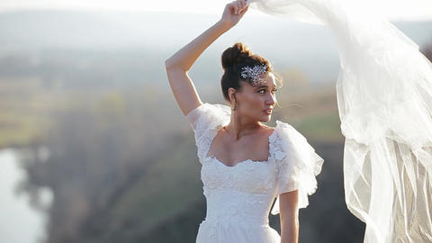 Beautiful bride in a luxurious white dress is standing in deserted field on Live Action
