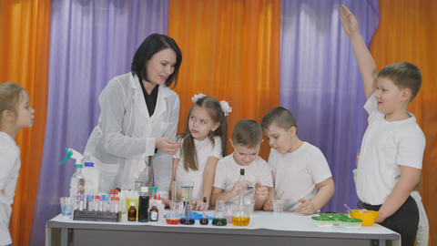 Chemical experiments for children. Boy adds green drops to a clear glass of Live Action