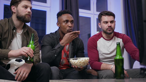 Front view of good-looking serious young multiethnic men which eating popcorn Live Action