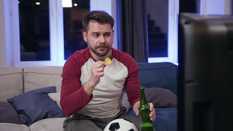 Slow motion of attractive emotional bearded guy which drinking beer ,eating Live Action