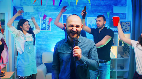 Attractive bald man doing karaoke at wild party with neon lights Live Action