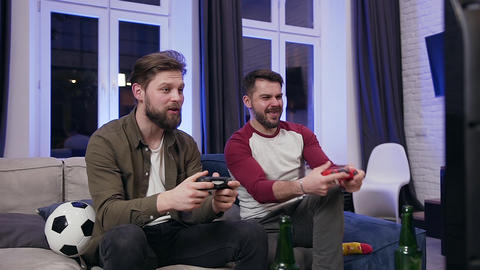 Handsome excited bearded 30s men enjoying video games and celebrating joint Live Action