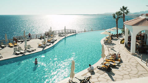 Timelapse of swimming pool at resort. Young girls relaxing on deck chairs Live Action