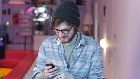 Smiling young man reads mobile phone messages photos laughing Live Action