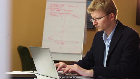 Working blond businessman in glasses with laptop printing e-mail Footage