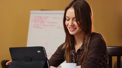 Smiling beautiful attractive young woman reads tablet PC office Footage
