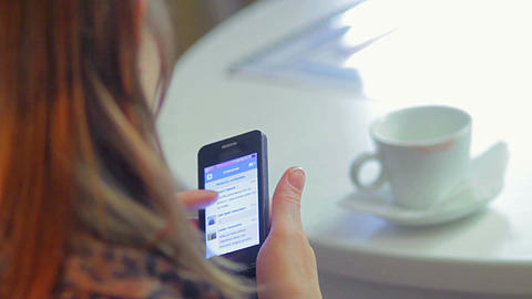 Woman writes sms types mobile phone message in cafe conversation Live Action