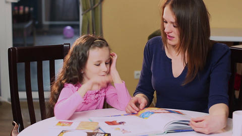 Happy mother teaches little daughter color book, learning colors Footage