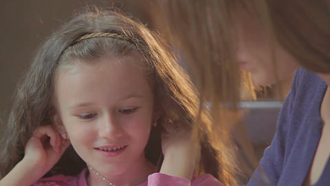 Smiling little girl daughter telling woman mother exciting story Footage