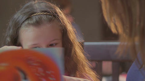 Little girl daughter smiling chatting her mother, reading book Footage