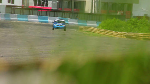 Sports car racing on track, view through the green grass Live Action