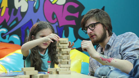 Young man father teaches smiling child girl, playing board game Footage